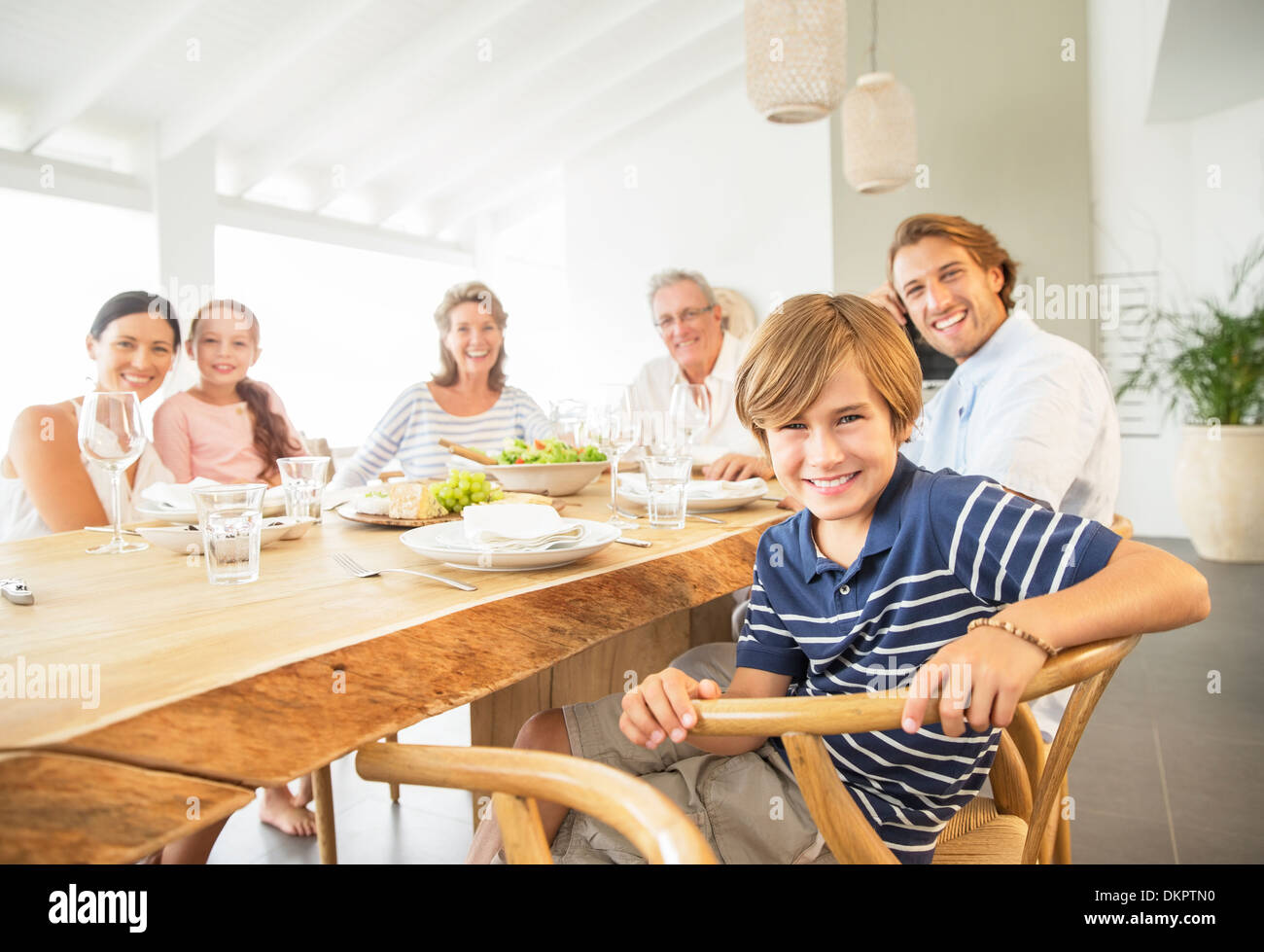 Family smiling together at table - Stock Image