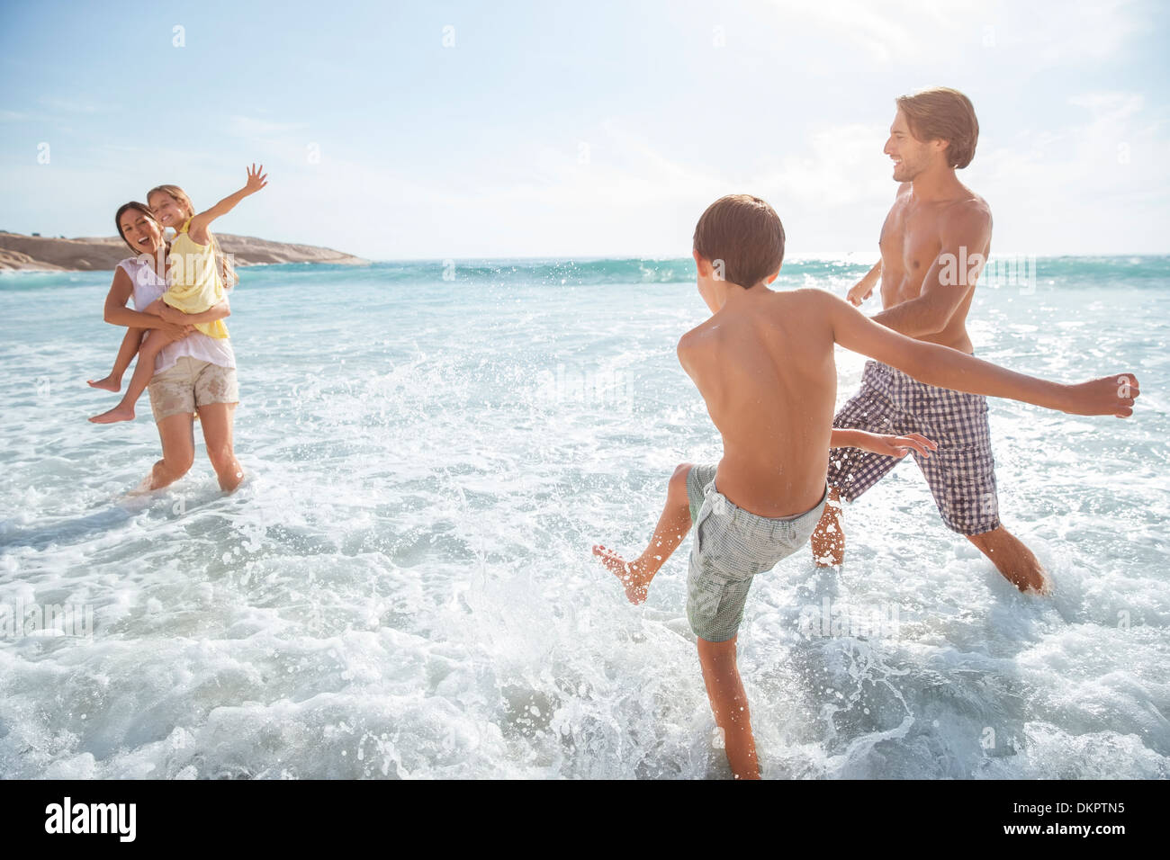 Family playing together in waves on beach - Stock Image