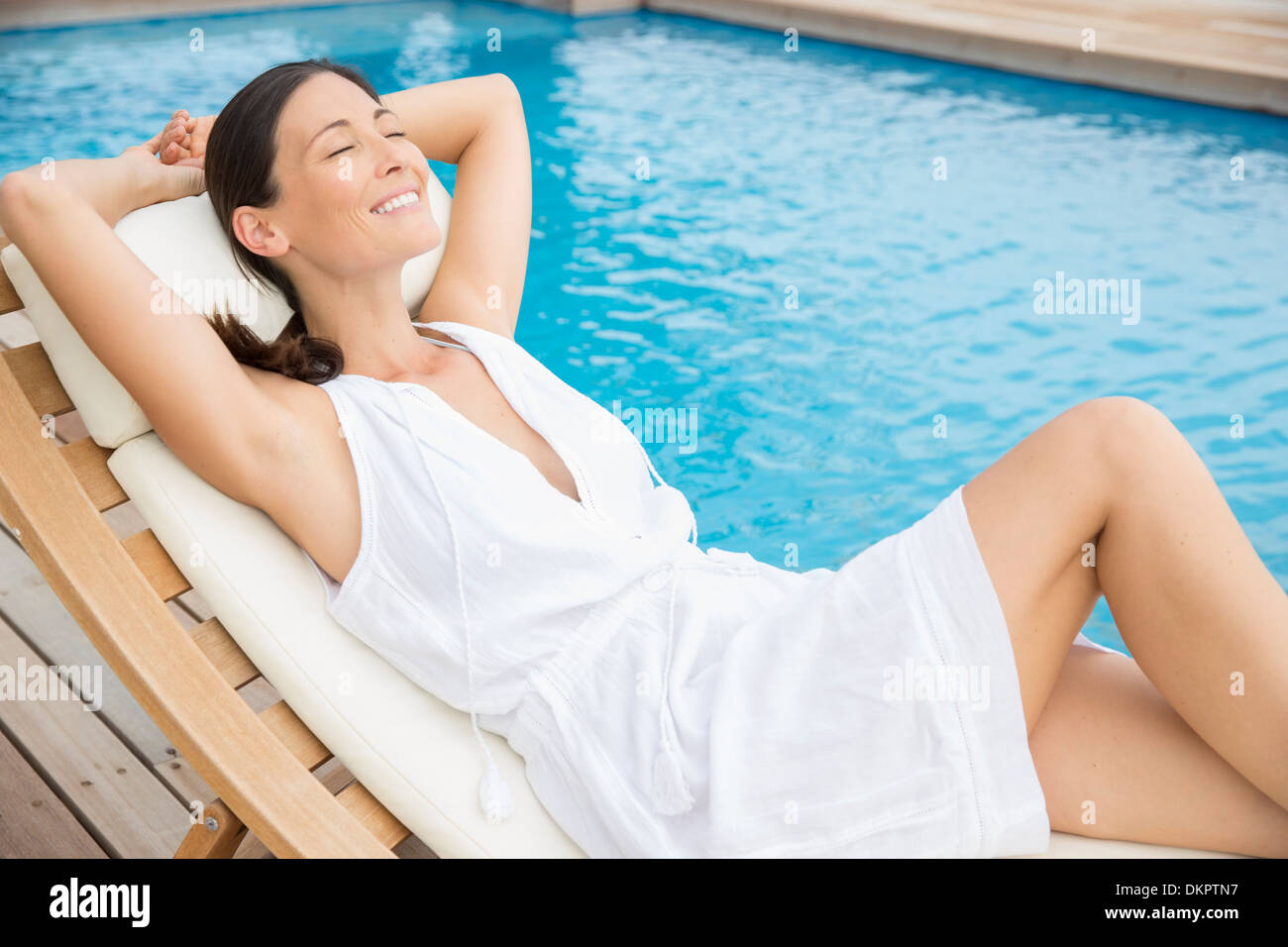 Woman relaxing by pool - Stock Image