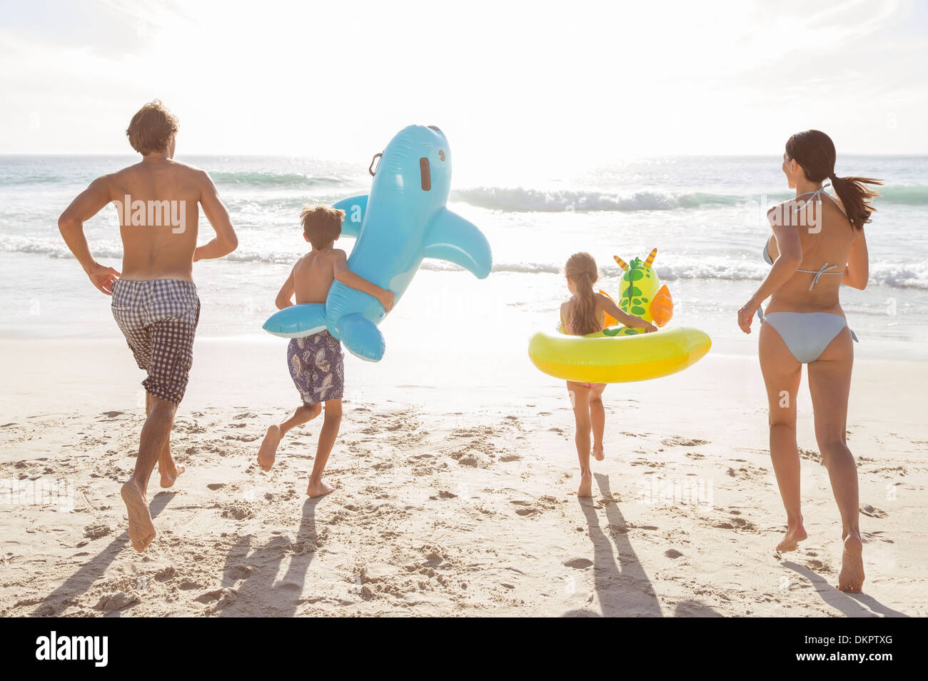 Family playing together on beach - Stock Image