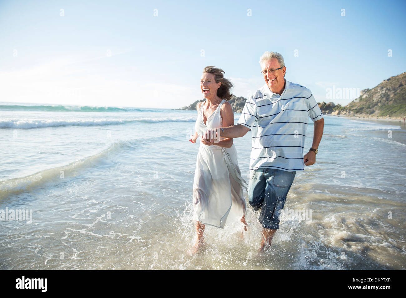 Older couple playing in waves on beach - Stock Image