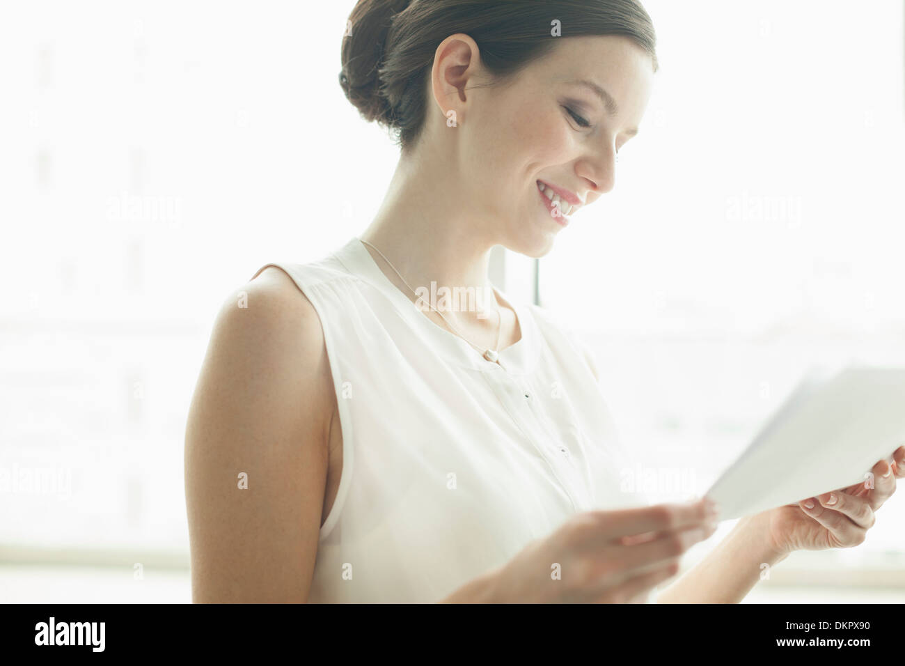 Businesswoman reading papers in office - Stock Image