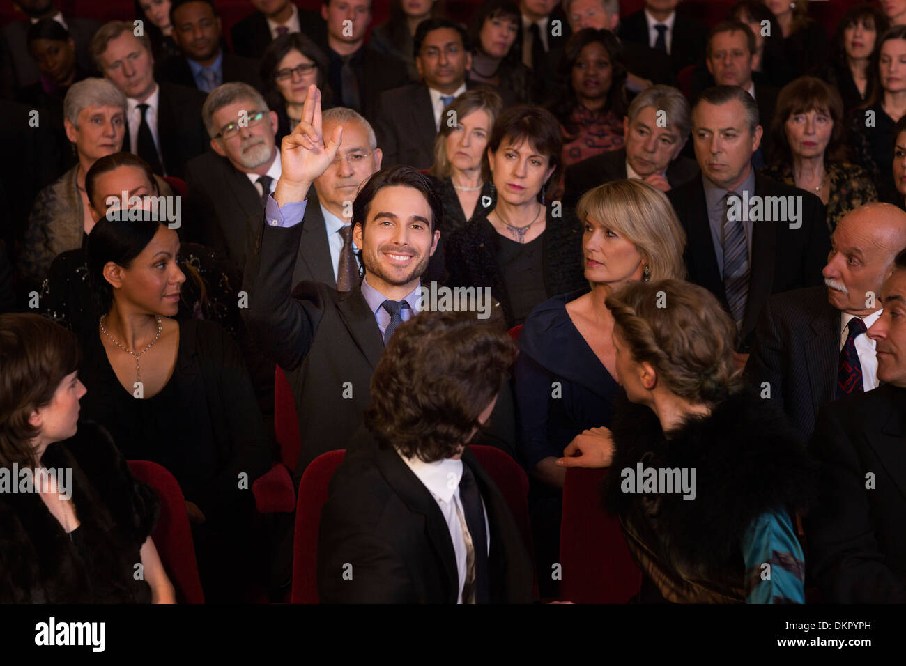 Man raising hand in theater audience - Stock Image