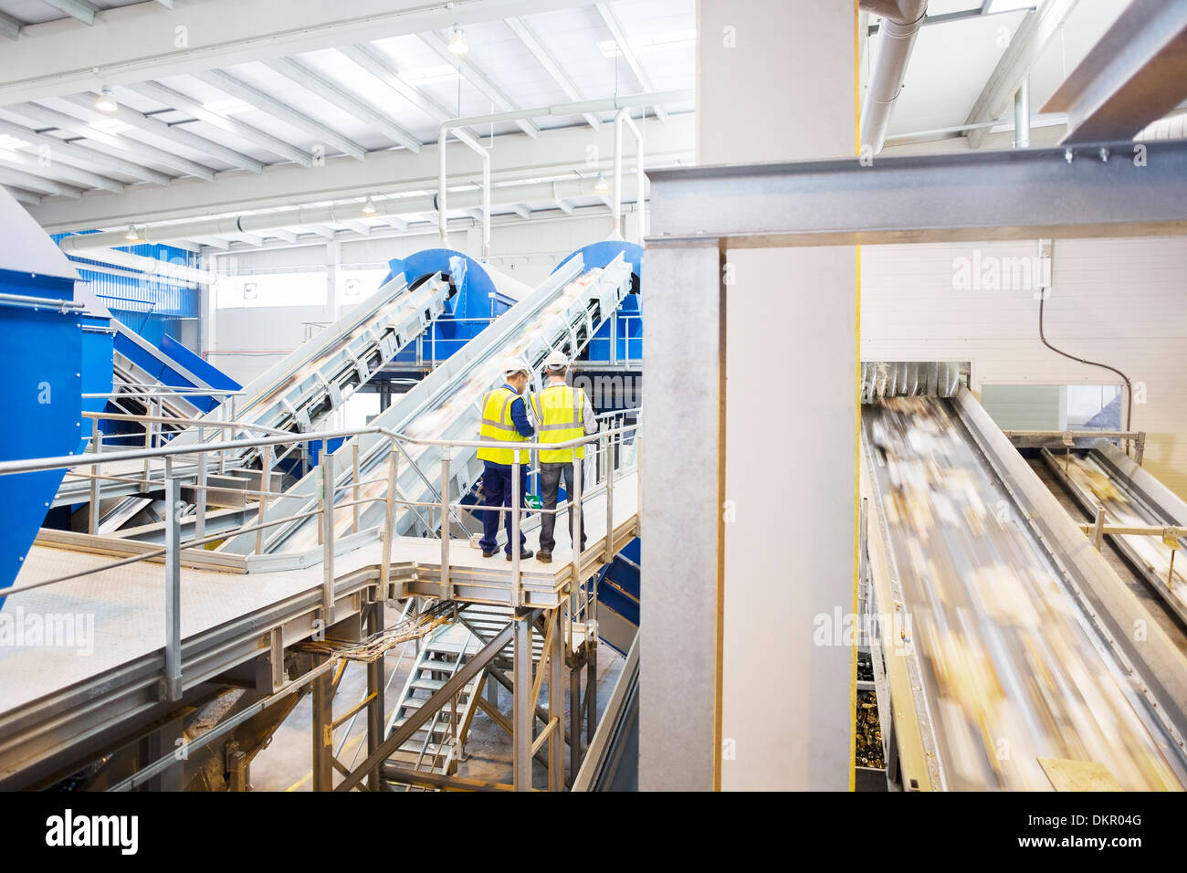 Workers talking on platform in recycling center - Stock Image