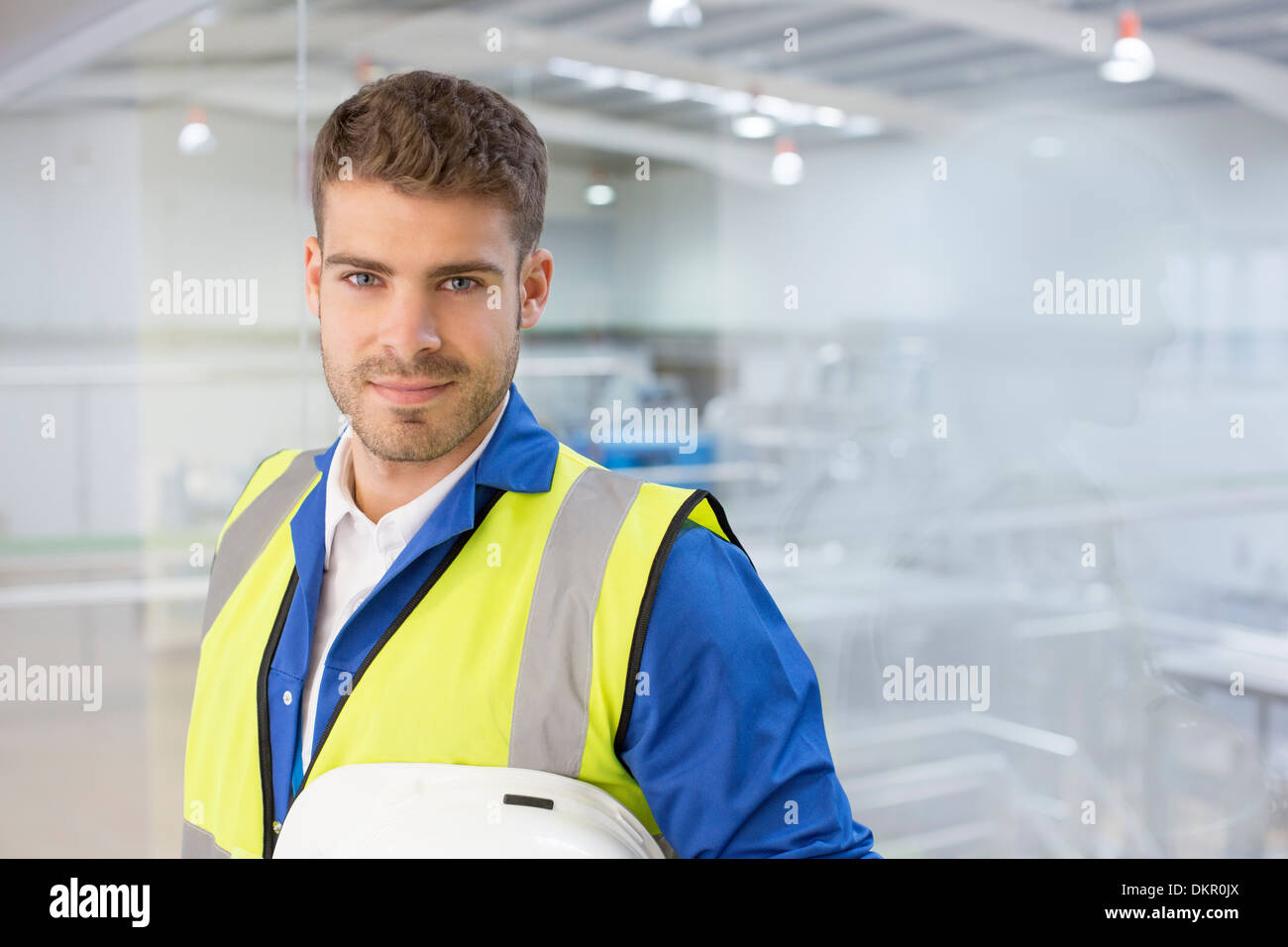 Worker smiling by window in factory Stock Photo