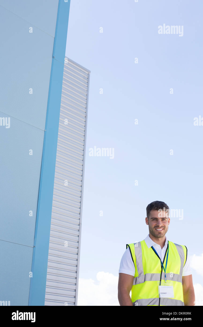 Worker smiling below highrise buildings - Stock Image