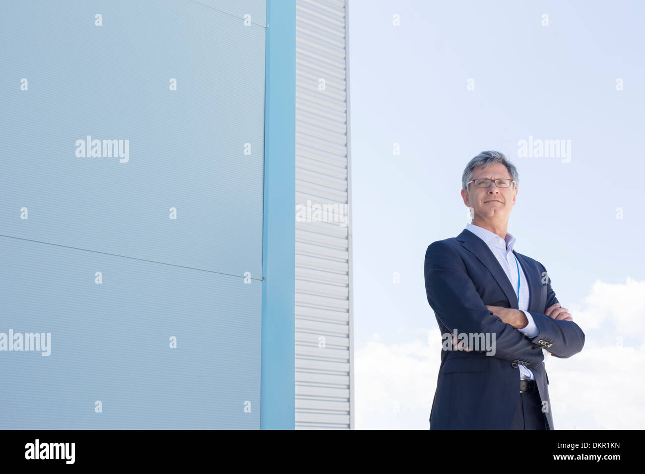Businessman standing below highrise buildings - Stock Image