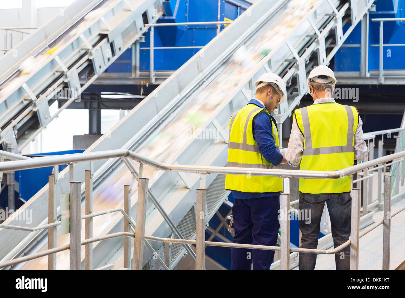 Workers talking in recycling center - Stock Image