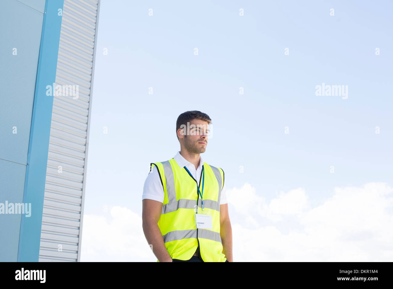 Worker standing below highrise building - Stock Image