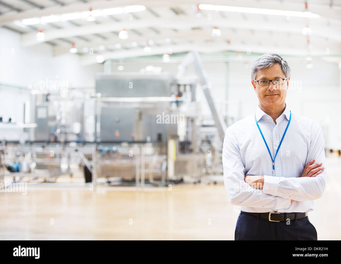Businessman smiling in factory - Stock Image
