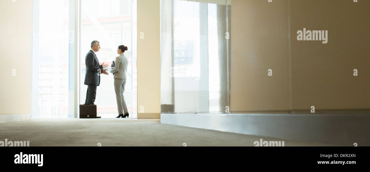 Business people talking at office window - Stock Image