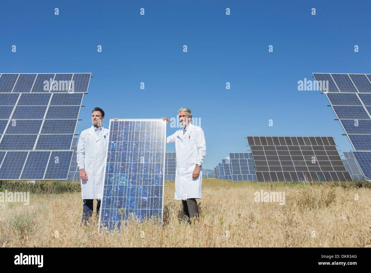 Scientists holding solar panel in rural landscape - Stock Image