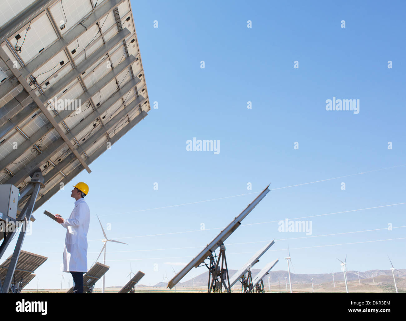 Scientist examining solar panel in rural landscape - Stock Image