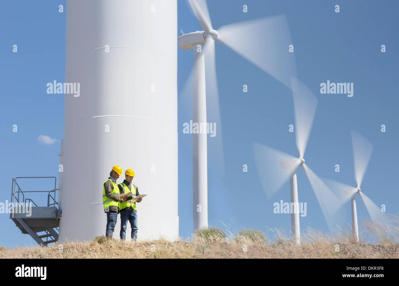 Workers talking by wind turbines in rural landscape - Stock Image
