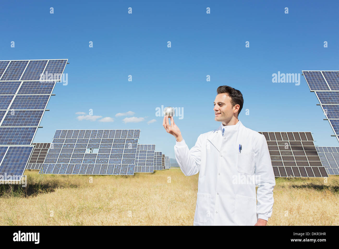 Scientist examining sphere by solar panels - Stock Image