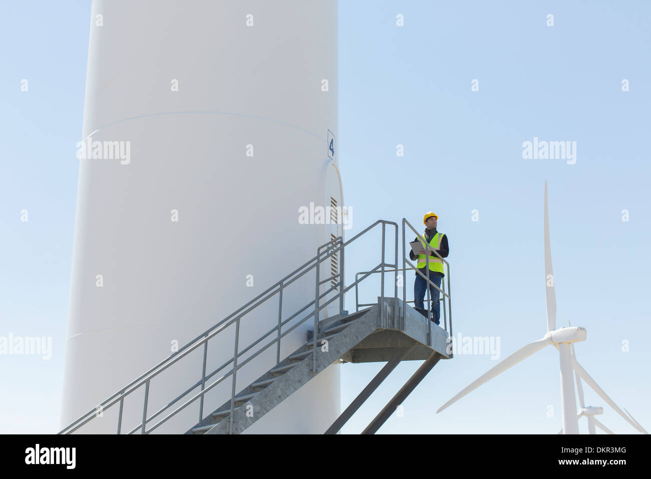 Worker standing on wind turbine - Stock Image