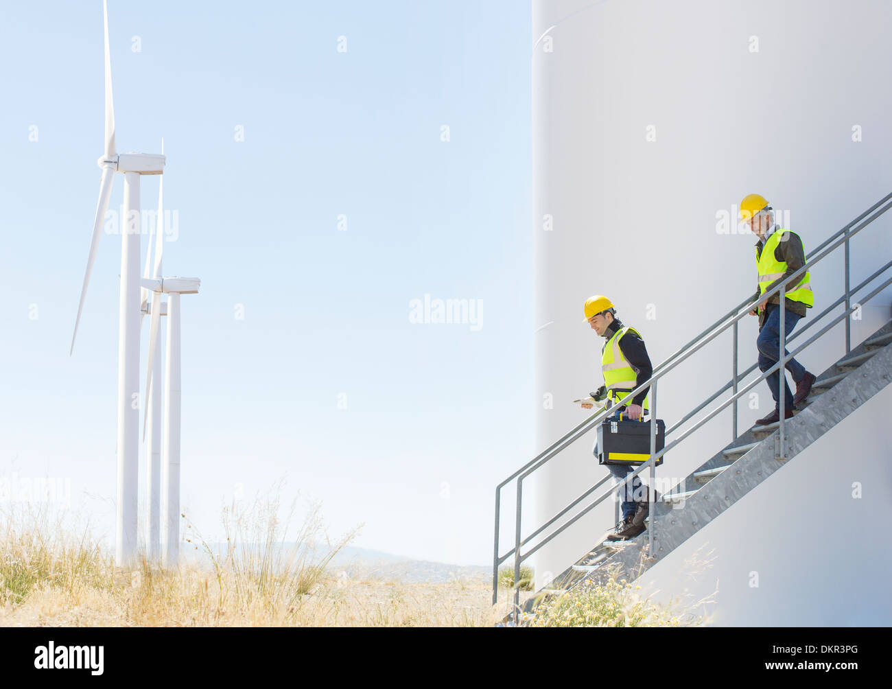 Workers on wind turbine in rural landscape - Stock Image