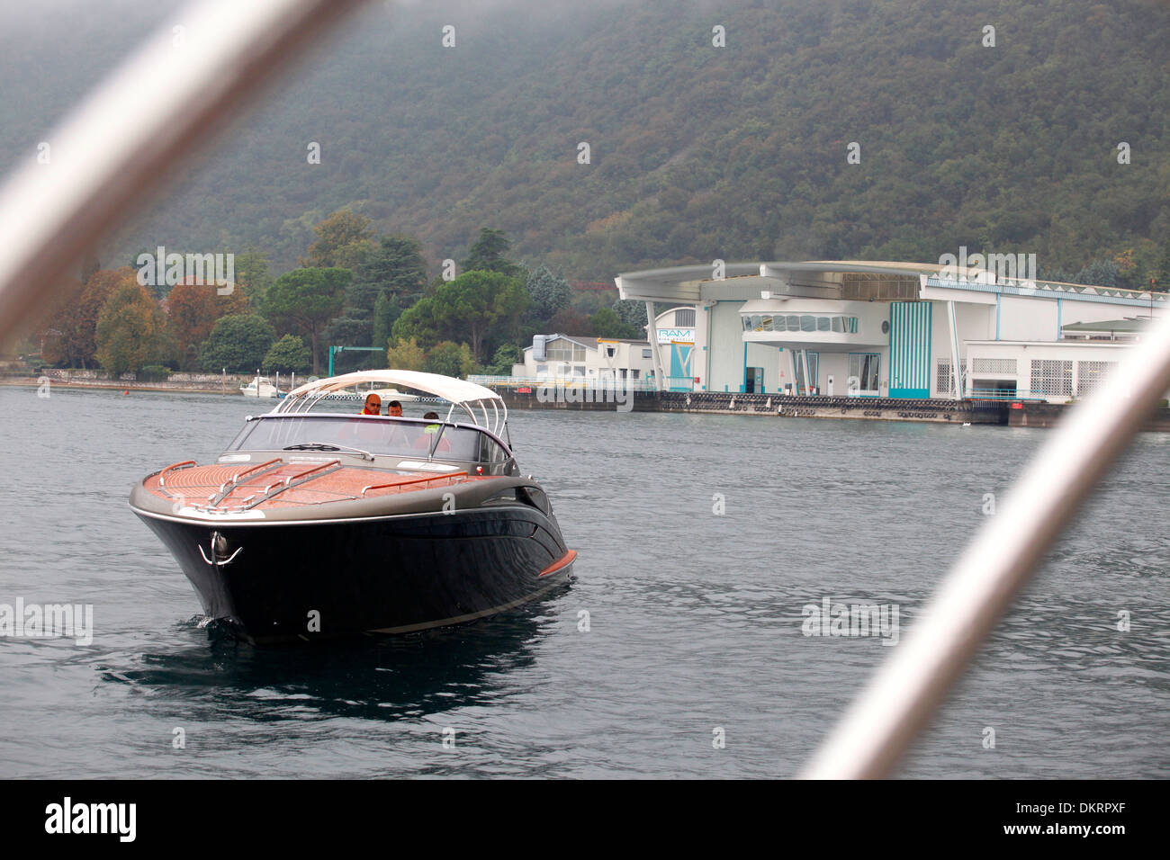 A Rivarama super yacht near the Riva factory on a misty Lake Iseo in Sarnico, Italy. - Stock Image