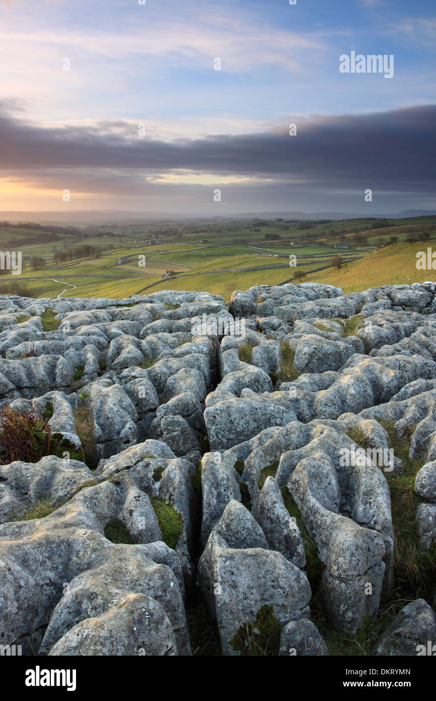 Sunrise over the weathered rocks at Malham Cove in the Yorkshire Dales National Park, England - Stock Image