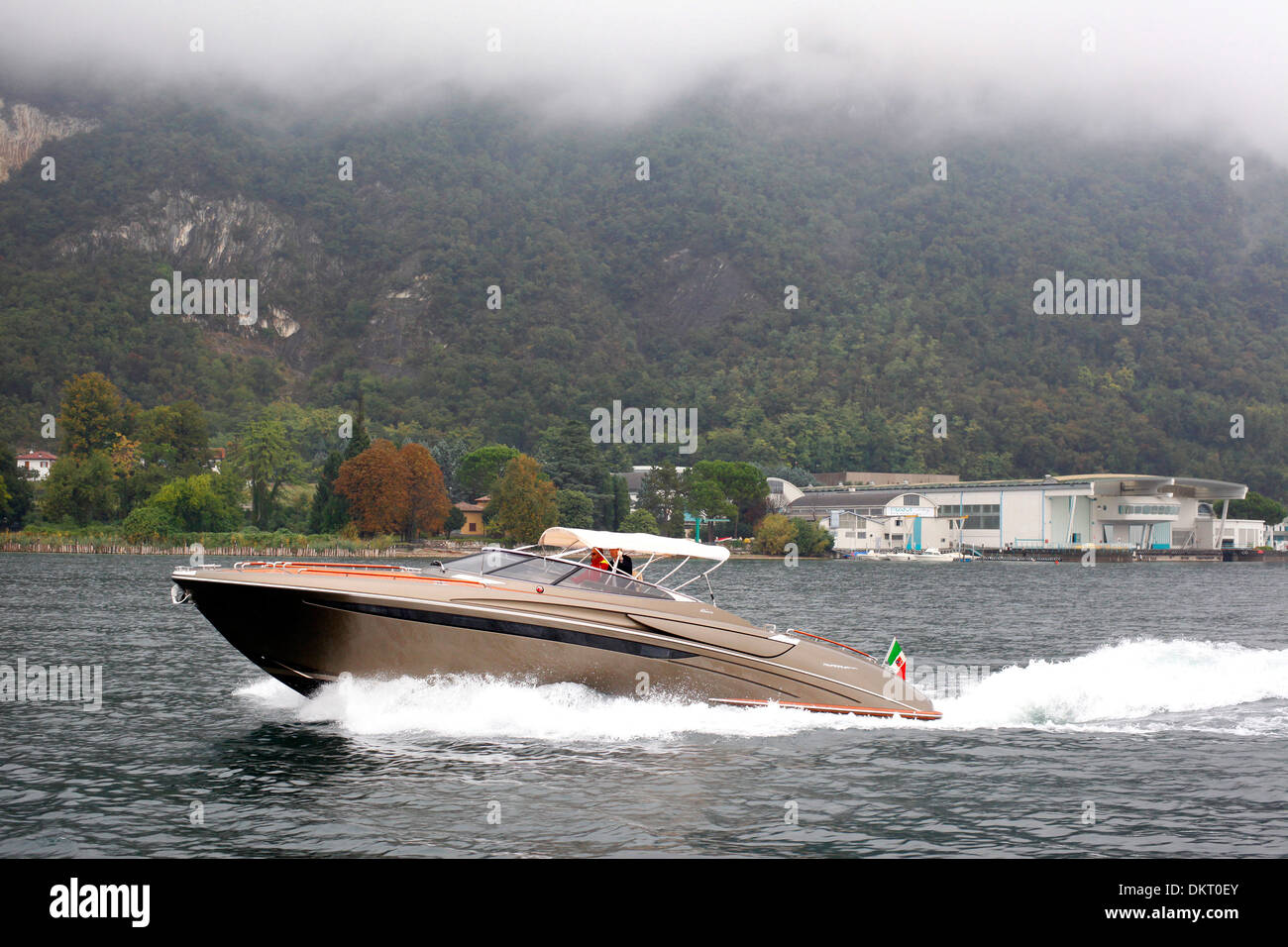 A Rivarama super yacht near the Riva factory on a misty Lake Iseo in Sarnico, Italy. - Stock Image