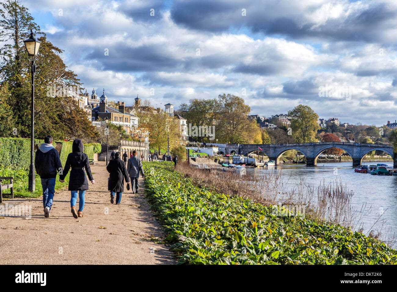A couple holding hands and people walking on the path next to the river Thames towards Richmond bridge Stock Photo