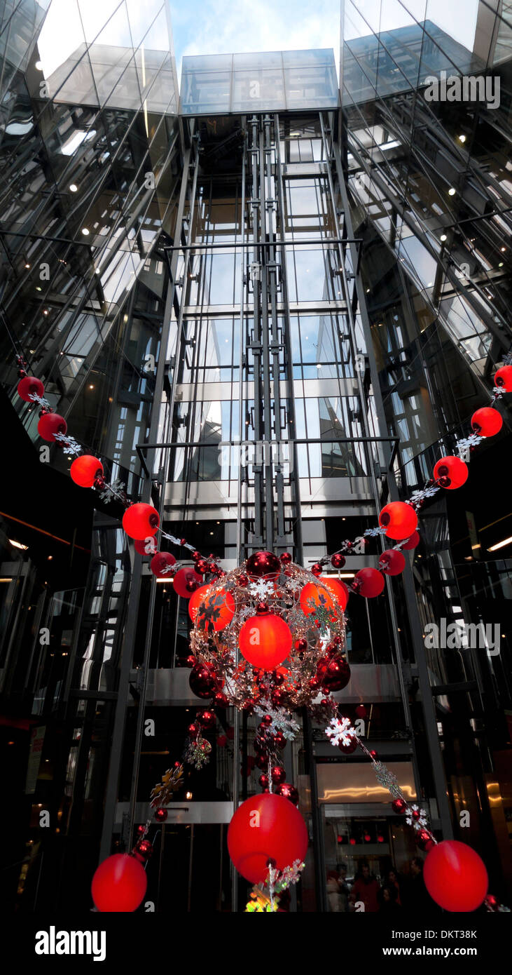 Red Christmas decorations in front of the elevator  lift at the entrance to One New Change shopping mall in Central London UK   KATHY DEWITT - Stock Image