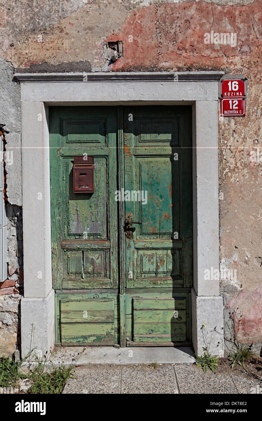 Door for house with fading peeling plaster, Kozina, Slovenia - Stock Image