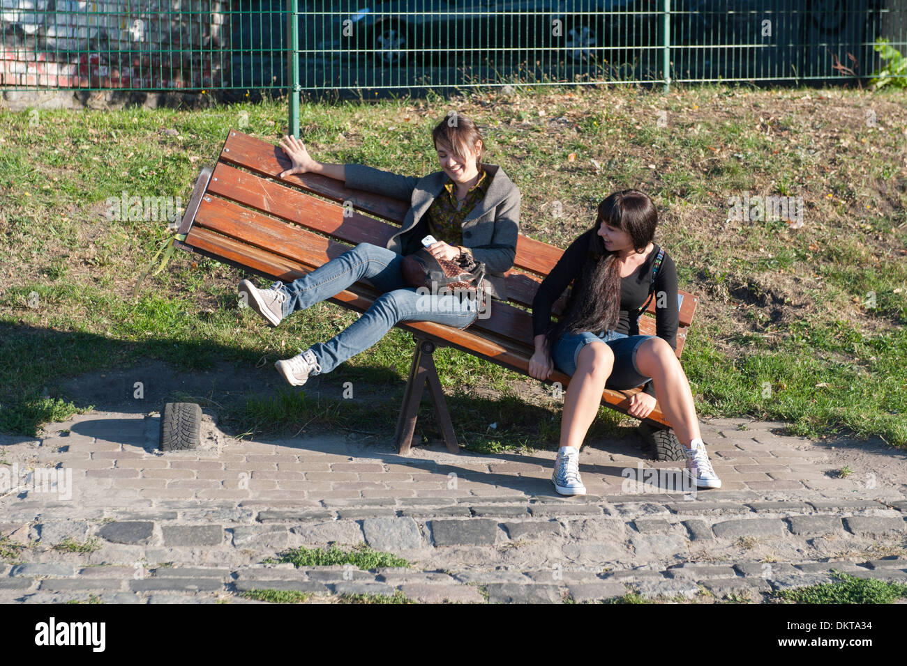Two girls goofing around on a seesaw park bench installation in Kiev Fashion Park in Kiev, the capital of the Ukraine. - Stock Image