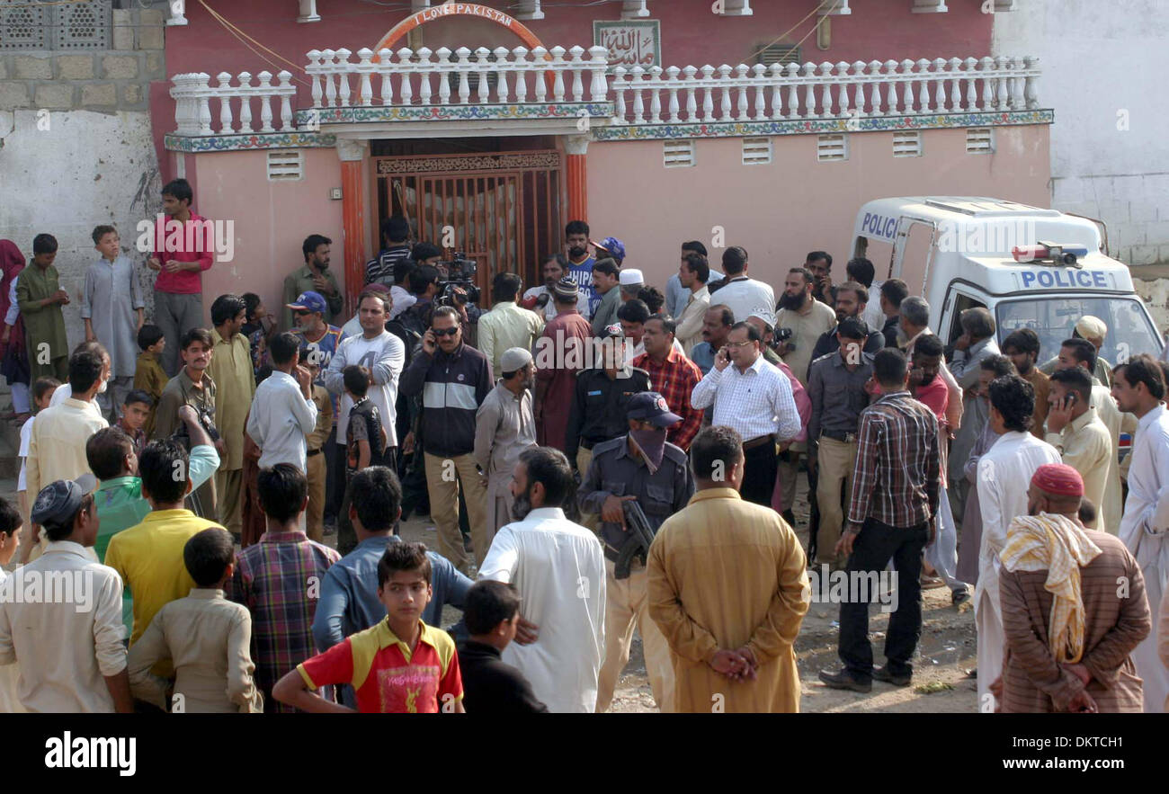 People gather near house where five person including three children died due to suffocation of poisonous gas, at Saeedabad locality of Baldia Town in Karachi on Monday, December 09, 2013. Police said died of gas suffocation after the room in which they asleep filled with gas after they forget to switch off generator. The deceased were identified as 40 years old Abrar, 35 years old his wife Uzma-35, and their three children, Hamza aged 12, Raza 4 and Samad 3. - Stock Image