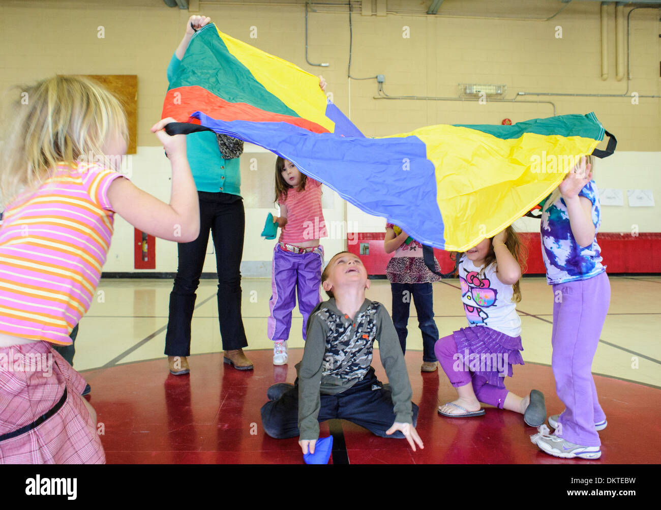 Pre-school children playing with rainbow parachute in gym - Stock Image