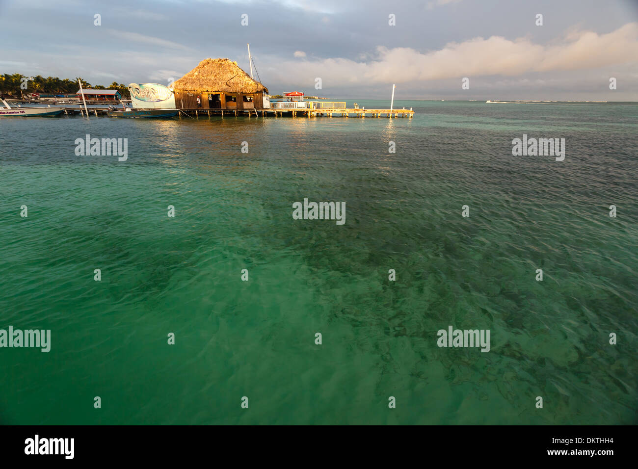 Beautiful turquoise water of Caribbean sea extend invitingly to snorkelers before commercial dock on Ambergris Caye in Belize - Stock Image