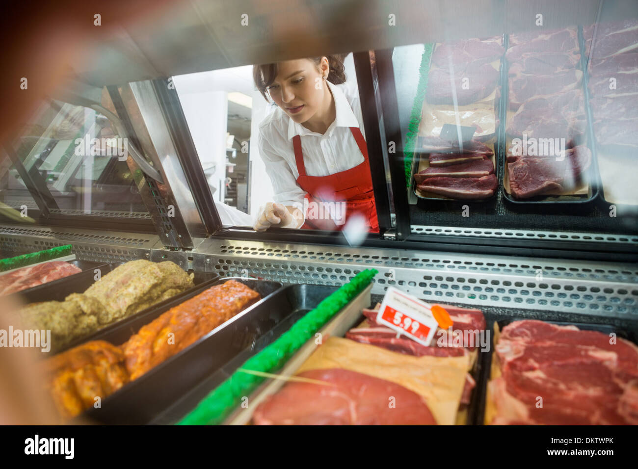 Saleswoman Looking At Variety Of Meat Displayed In Shop - Stock Image