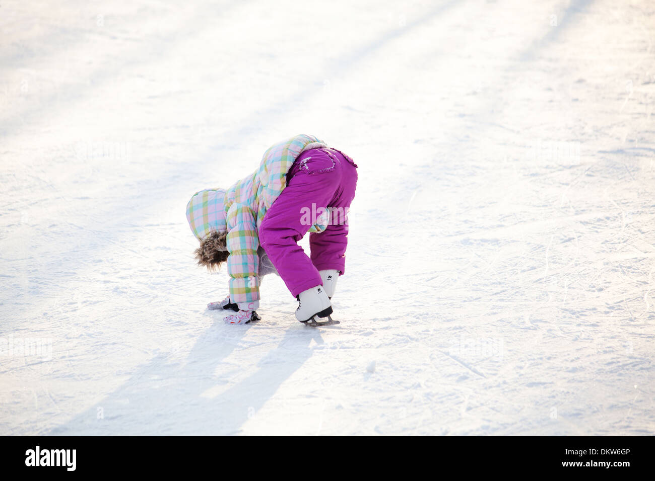 Little child learning how to ice skate - Stock Image