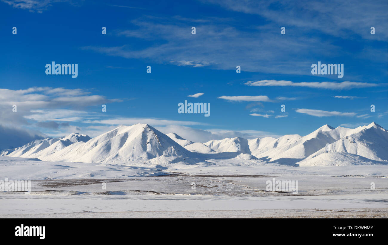 Snow covered Brooks Range mountains Alaska USA with blue sky from the Dalton Highway - Stock Image