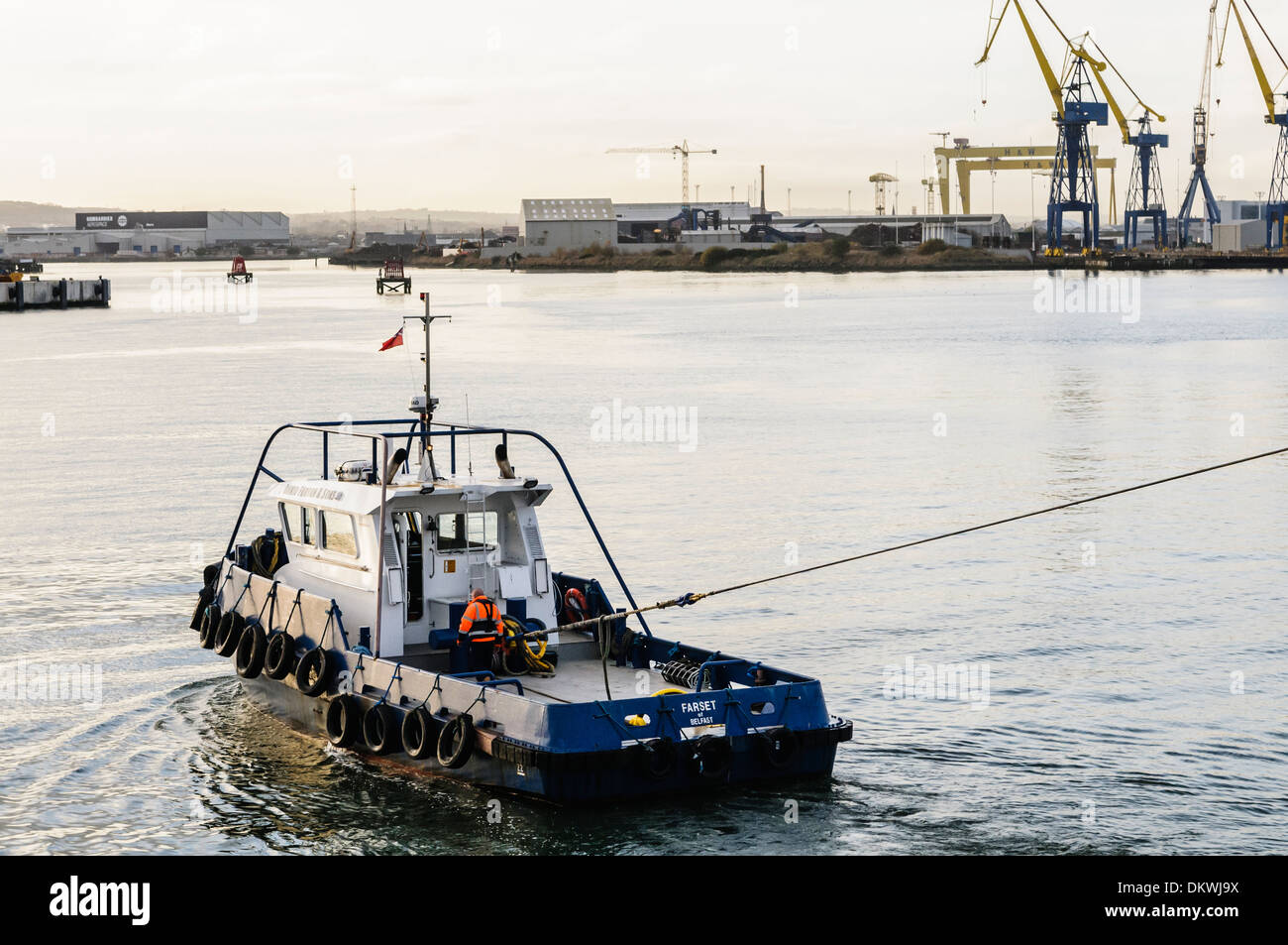 The tug boat 'Farset' pulls a ship into The Port of Belfast - Stock Image