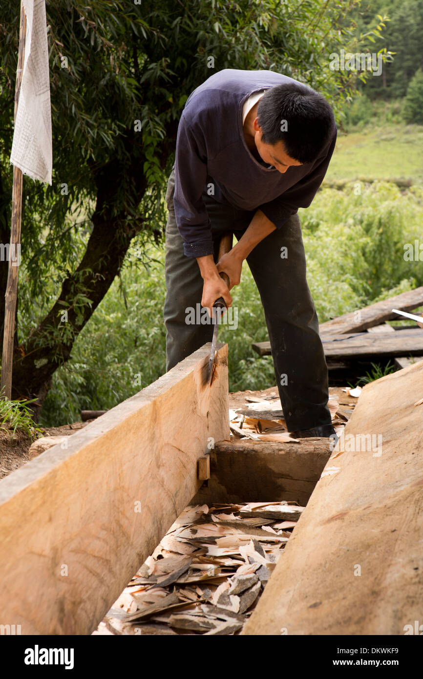 Bhutan, Bumthang Valley, Gaytsa Village, carpenter hand shaping house floorboards - Stock Image