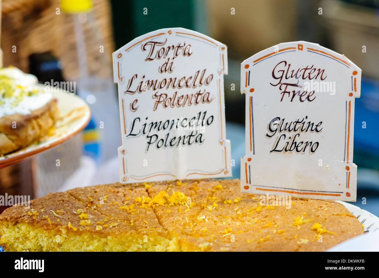 Limoncello polenta (torta di limoncello e Polenta) on a market stall with 'Gluten Free' sign (with an incorrect translation into Italian) - Stock Image