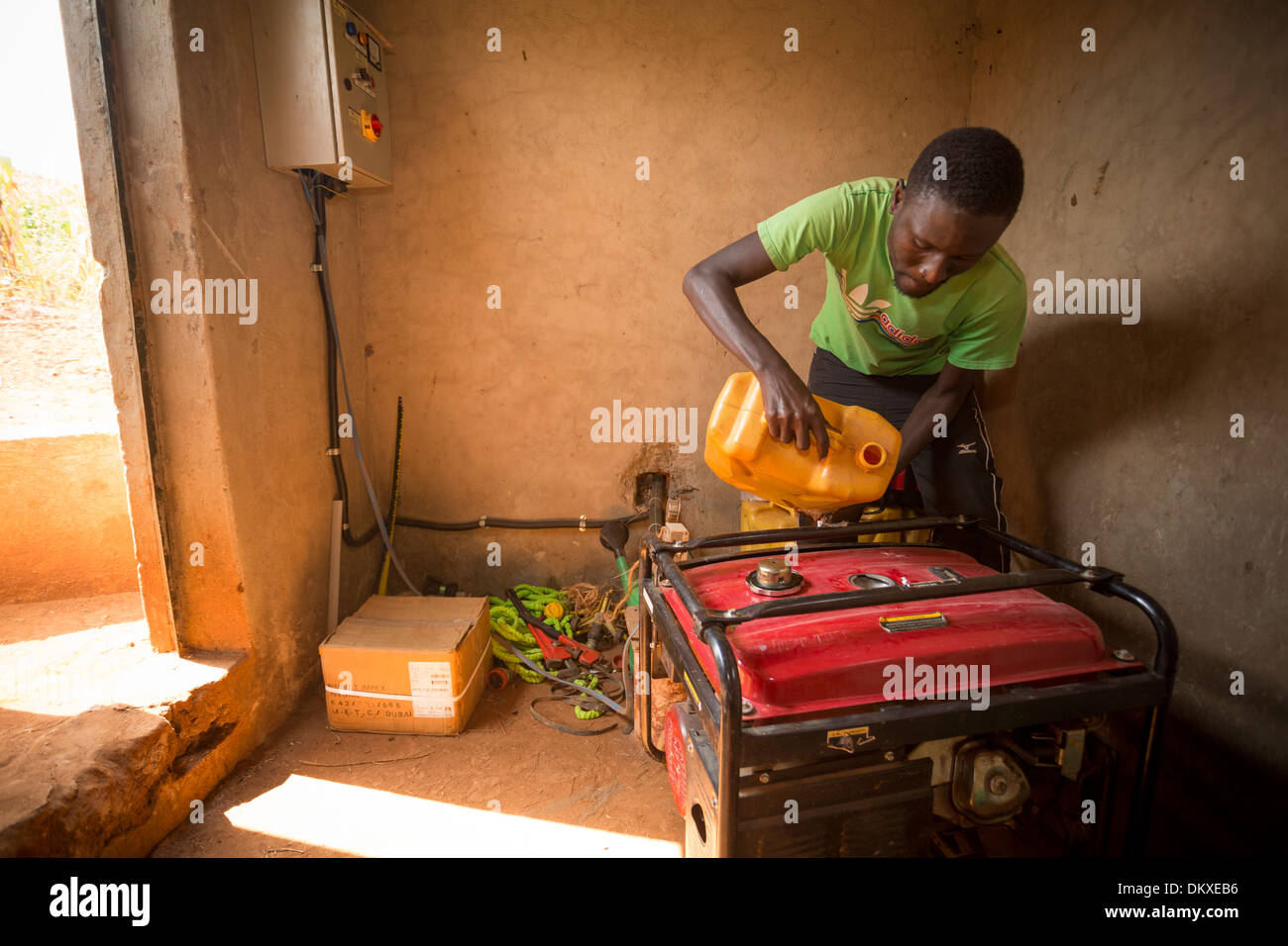 A man fuels a gasoline-powered generator in Gombe, Uganda, East Africa. - Stock Image