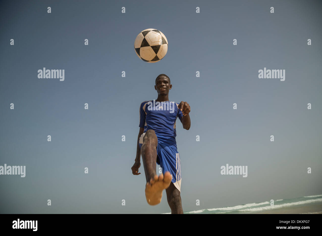 Football player on the beach in Dakar, Senegal. - Stock Image