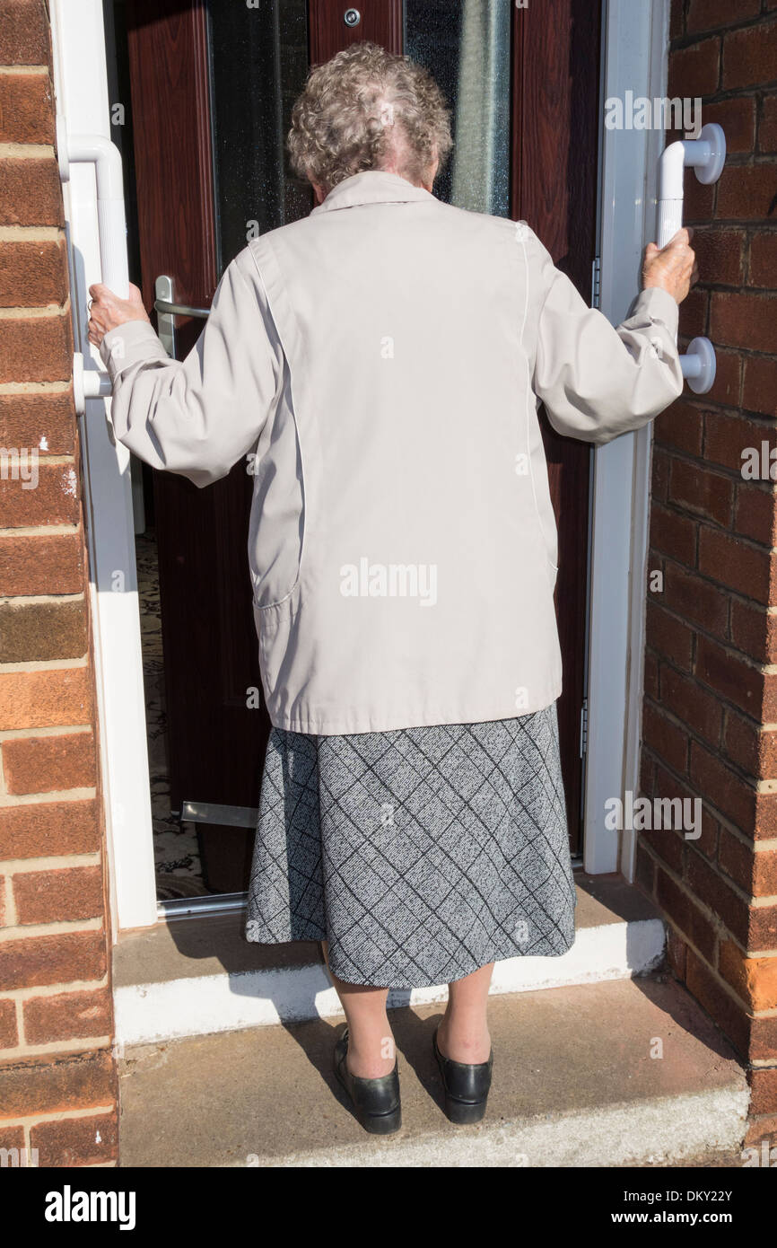 Elderly lady in her nineties using grab rails to enable her to climb step leading to house door. UK - Stock Image