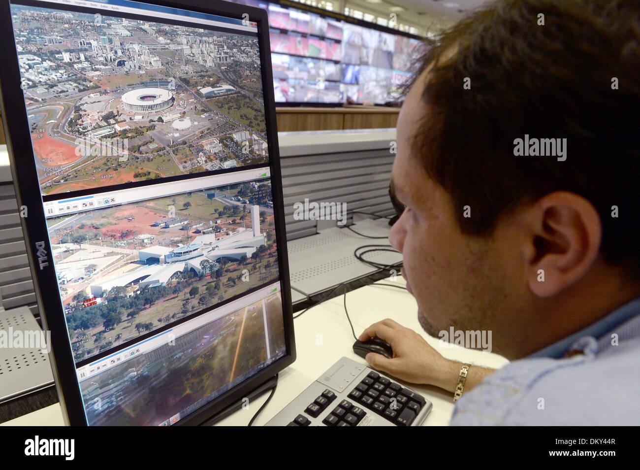 Ein Mitarbeiter überwacht am 09.12.2013 Videoaufzeichnungen und Videokameras rund um das Stadion «Stadion Nacional Mane Garrincha» im SESGE (Extraordinary Security Secretariat for Major Events) des Justizministeriums in der brasilianischen Hauptstadt Brasilia. Das Estadio Nacional Mane Garrincha ist eines der Stadien während der Fußball-Weltmeisterschaft 2014 in Brasilien. Foto: Marcus Brandt/dpa - Stock Image