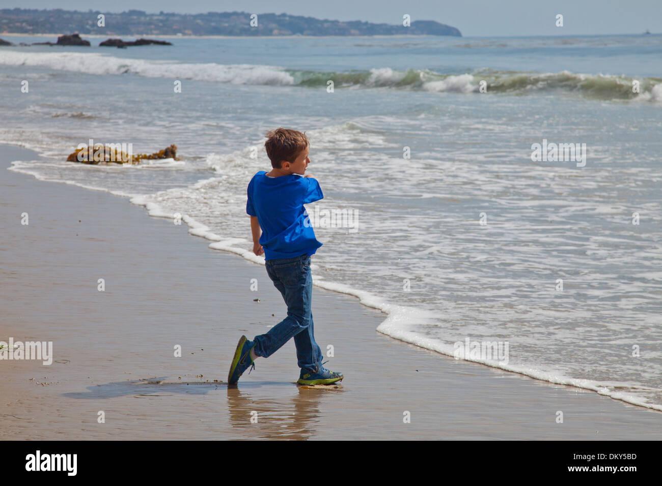 Boy throwing skipping rocks, El Matador State Beach, Malibu, Los Angeles County, California (MR) - Stock Image