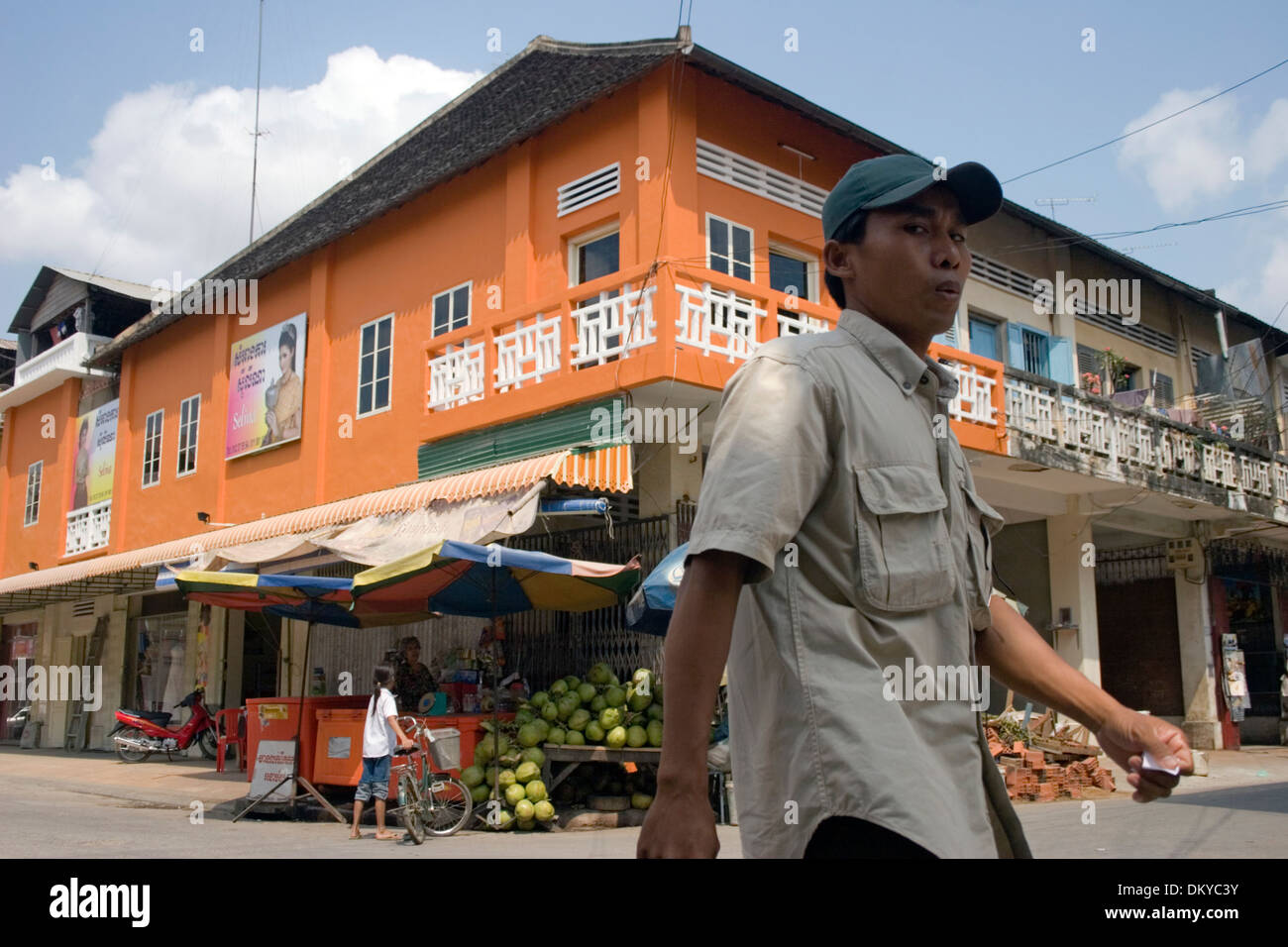 A man is walking past a bright orange building on a city street in Battambang, Cambodia. Stock Photo