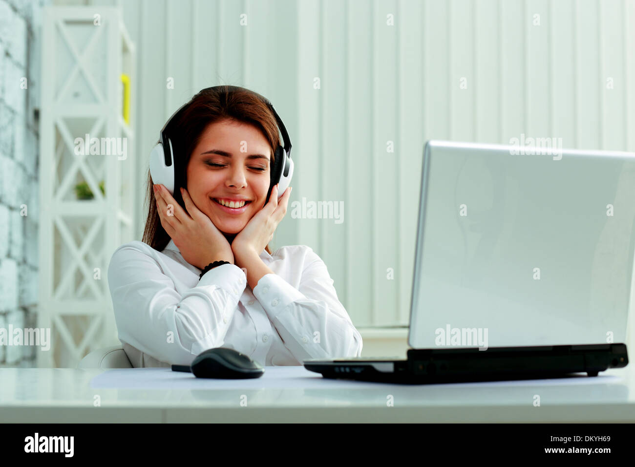 Young beautiful businesswoman listening music in headphones at office Stock Photo