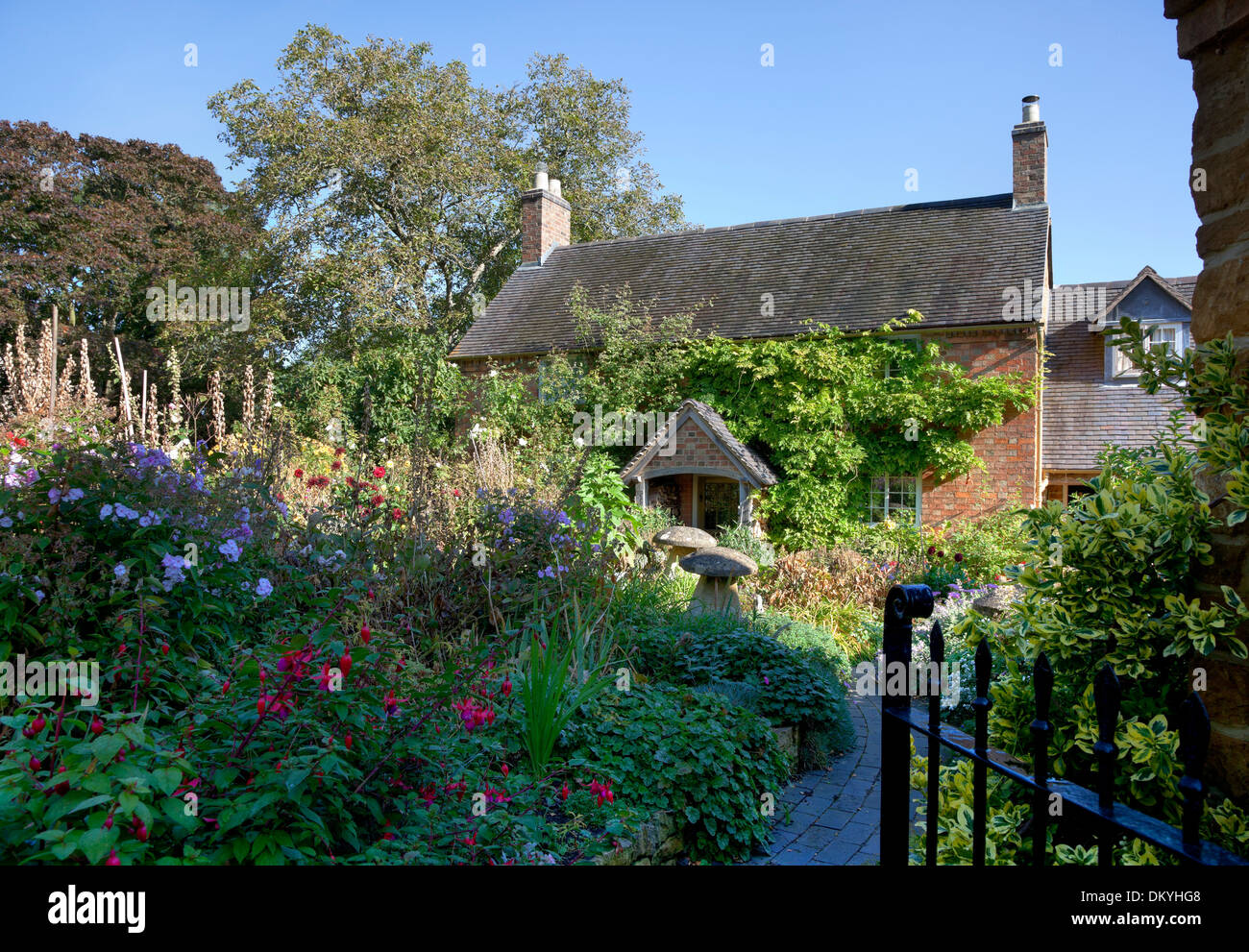 Pretty cottage with garden full of flowers, Warwickshire, England. - Stock Image