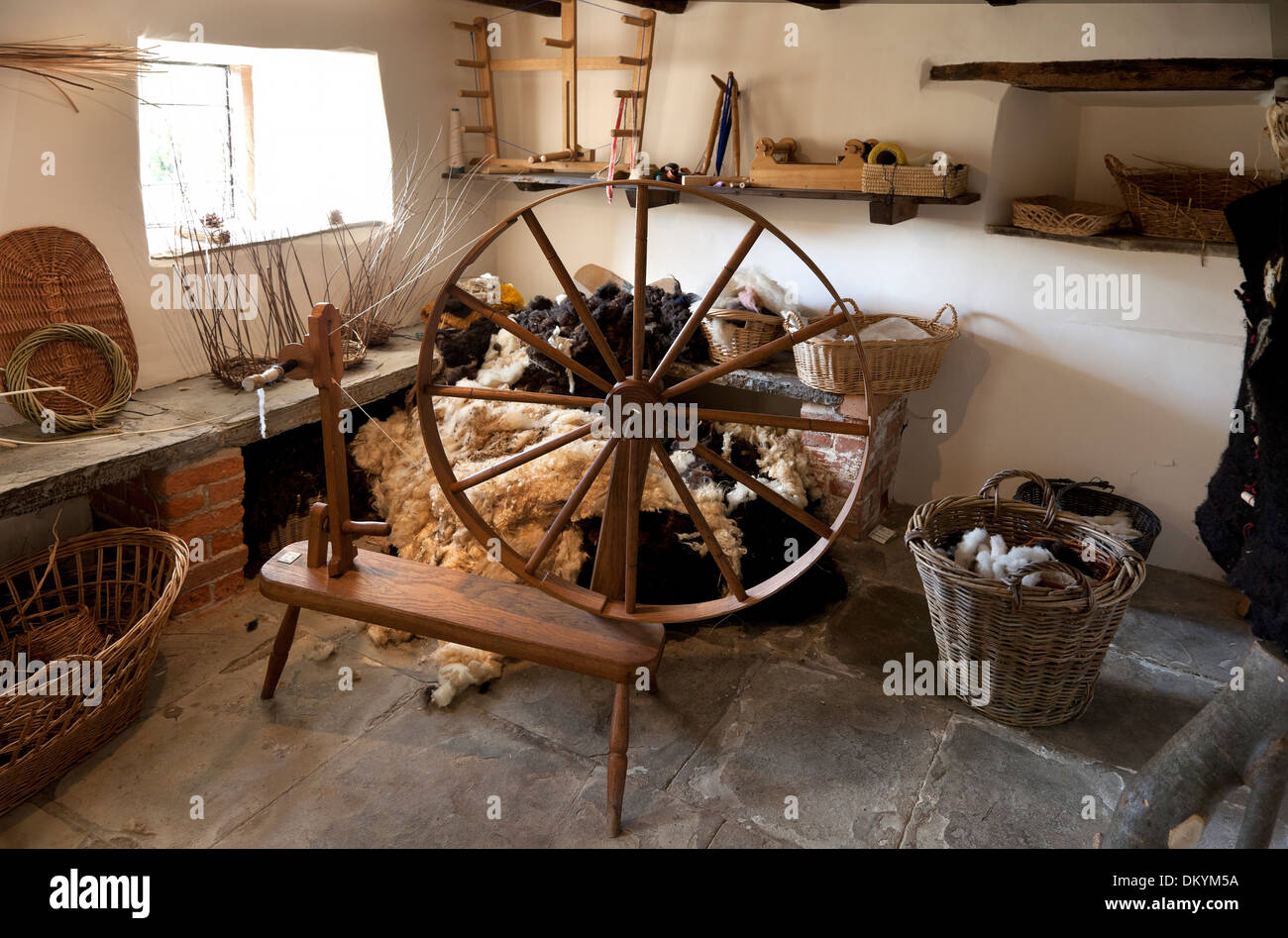 Traditional workshop with spinning wheel, fleece and baskets, England. Stock Photo