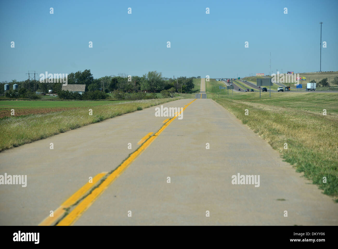 Old Route 66 snakes through Oklahoma, now often bypassed by new interstates the old two lane black top is left quiet - Stock Image