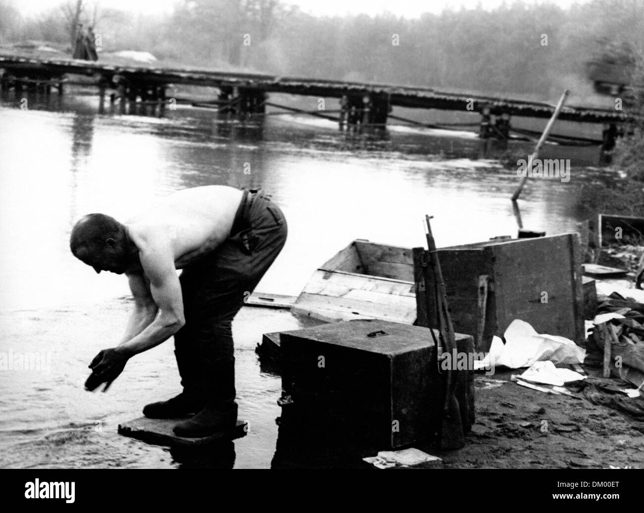 End of the war in Berlin in 1945 - A soldier washes himself in the Spree River at dawn, having put his rifle aside. Stock Photo