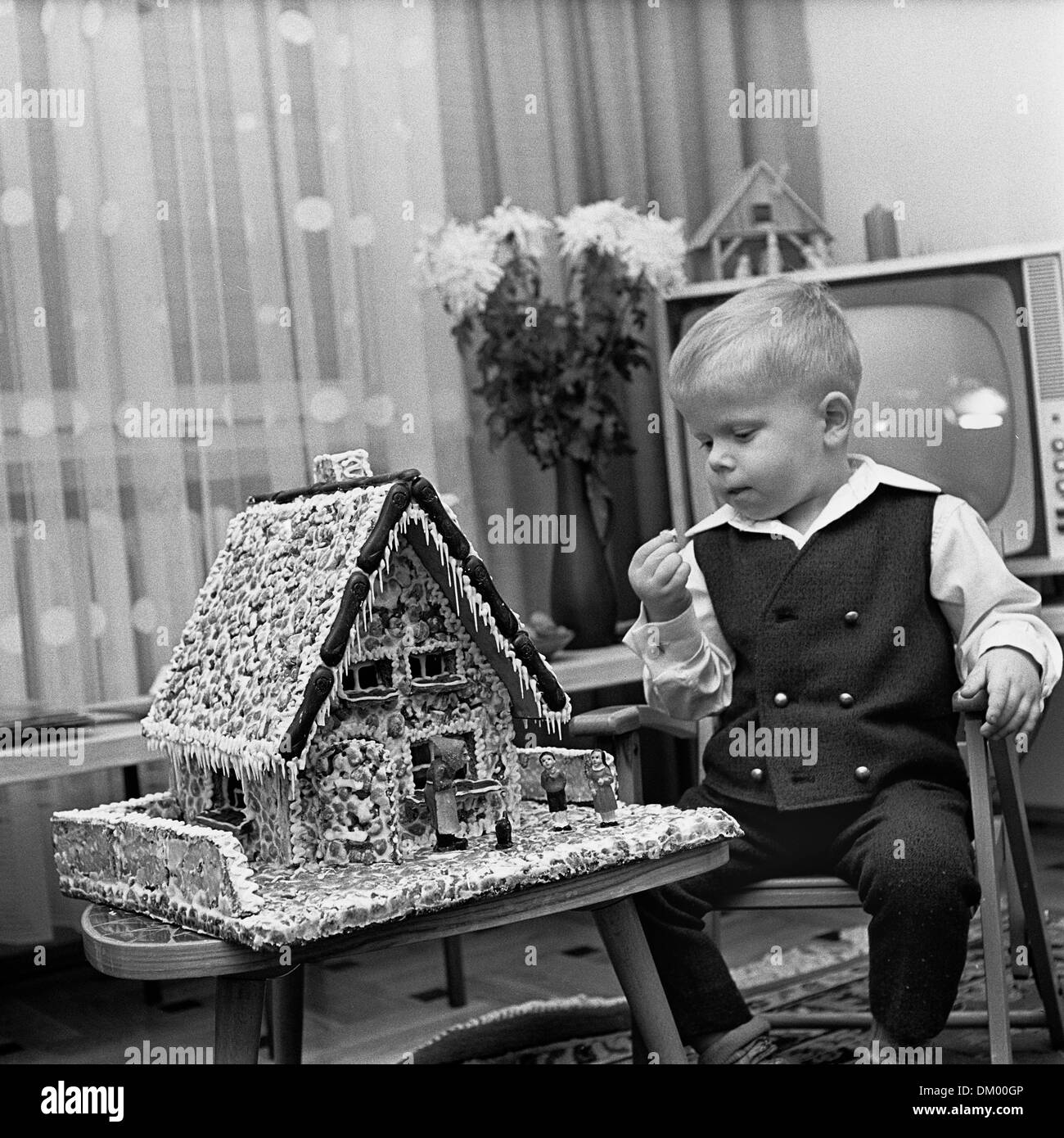 Wunderbar A Small Boy Sits Next To A Ginger Bread House And In Front Of A TV
