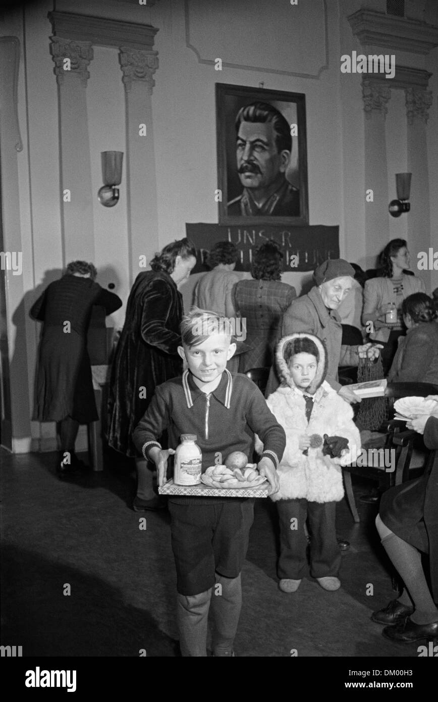 Children carry their presents under the Stalin portrait in the kindergarten of the Landespolizei during the Christmas celebrations, undated photograph (December 1950). Photo: Deutsche Fotothek/Erich Höhne, Erich Pohl - Stock Image